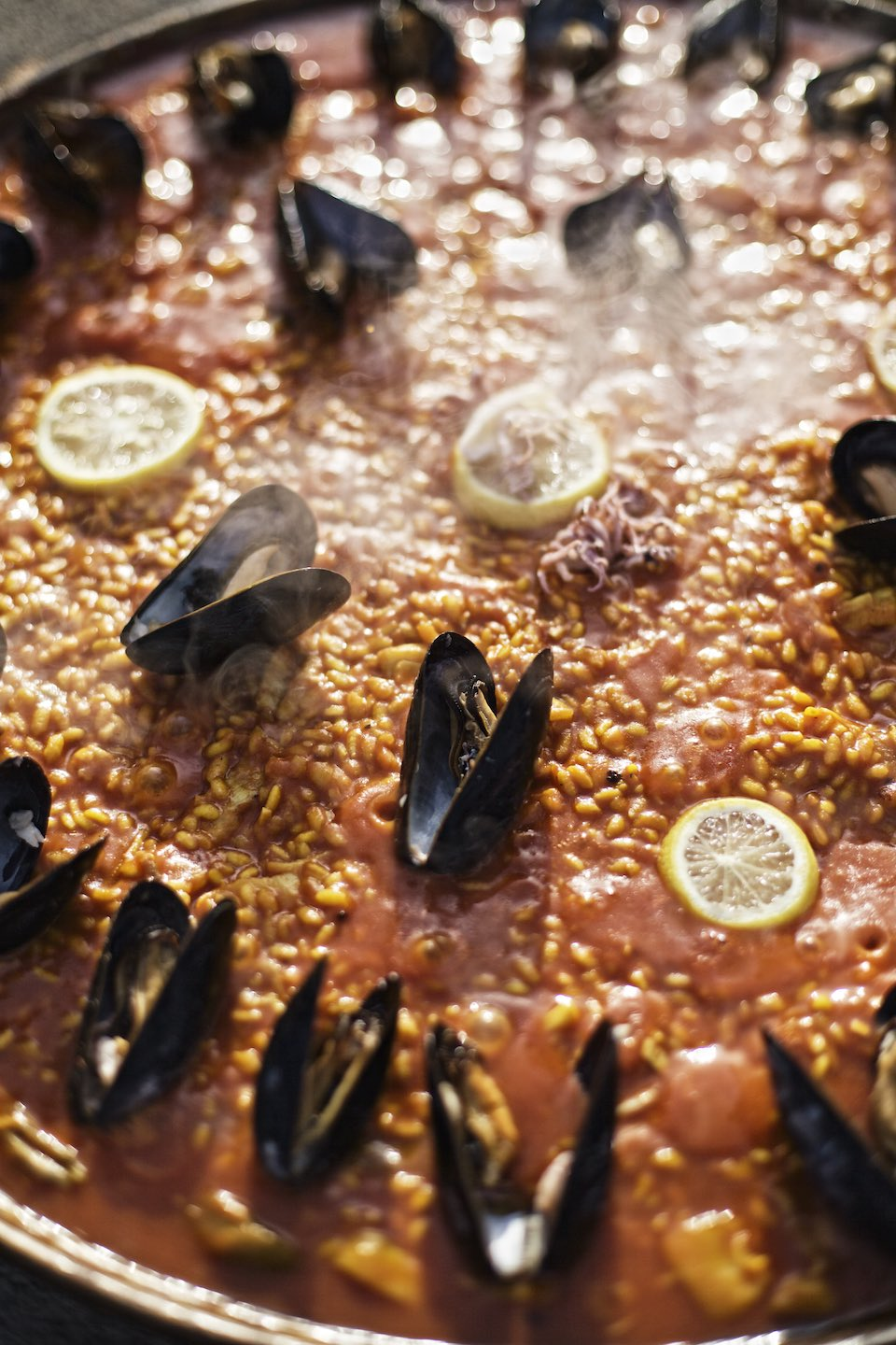 A steaming pan of seafood paella with mussels and lemon.