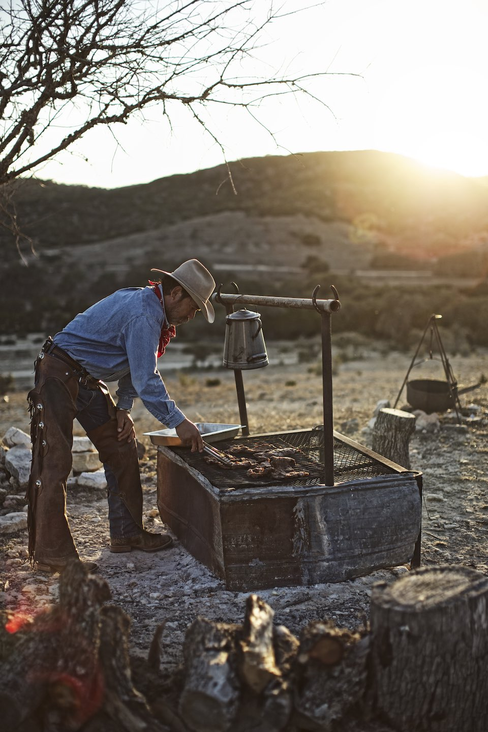 Cowboy cooking on an outdoor grill at sunset.