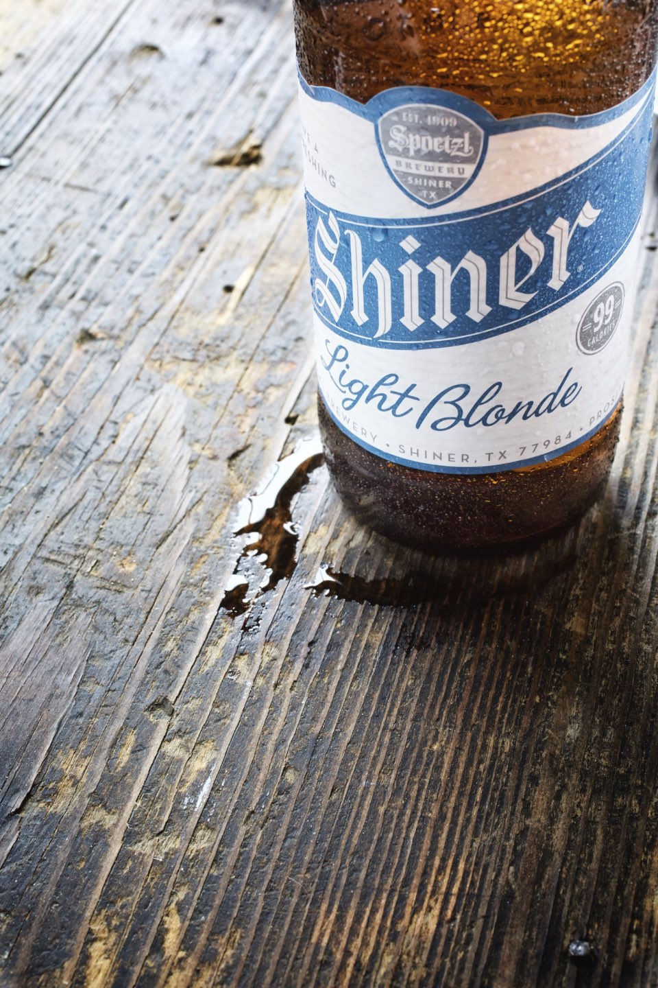 Cold Shiner beer leaving a ring of condensation on a wood table.