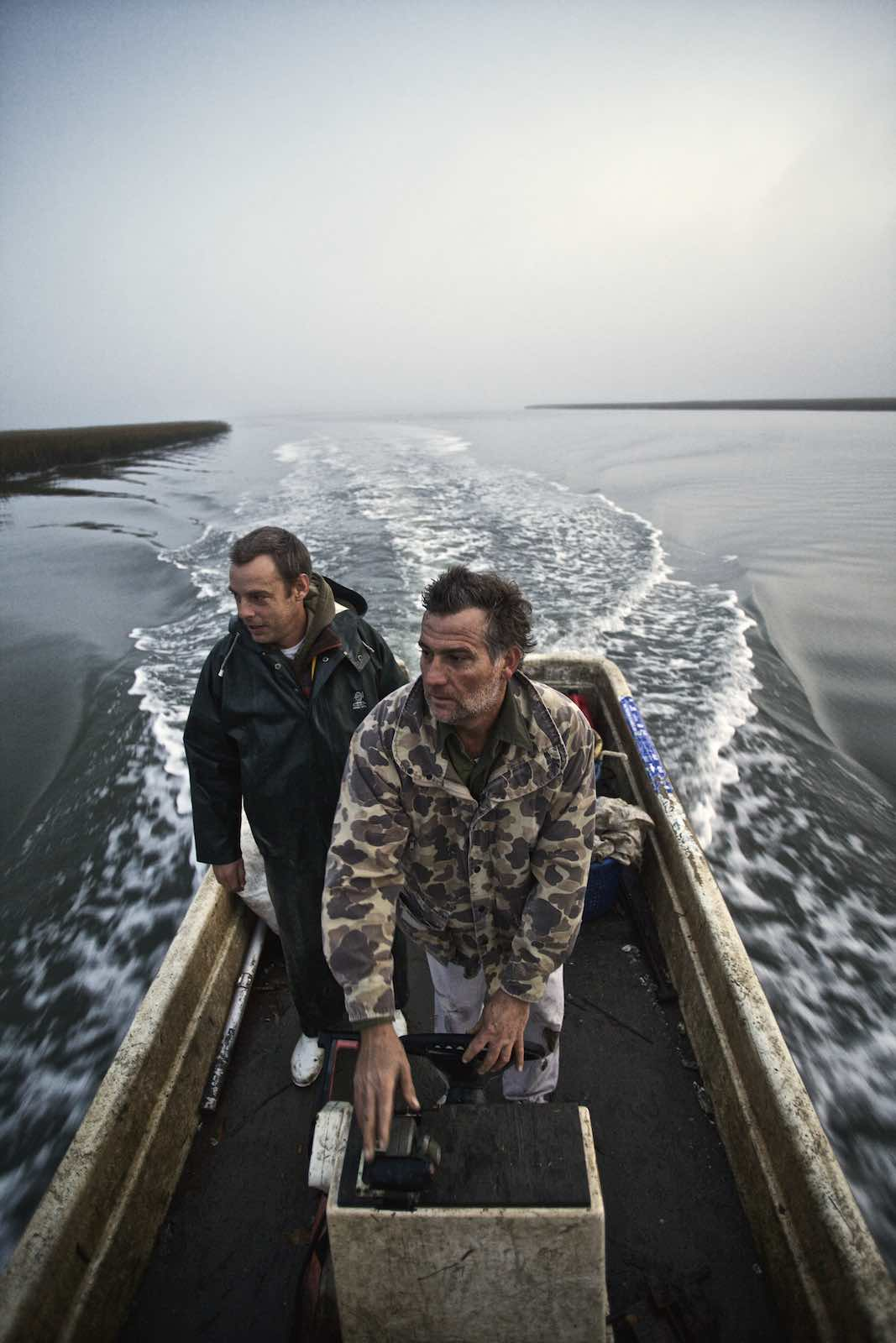Fishermen guiding their boat across dark waters.