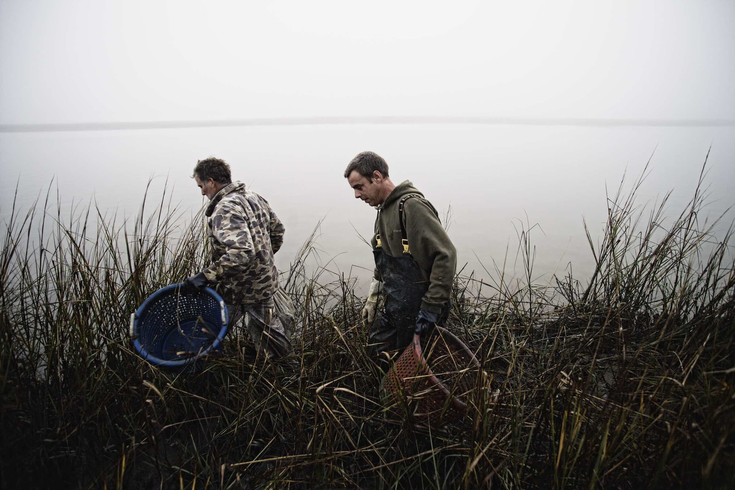 Jody Horton Photography - Fishermen carrying empty baskets through tall grass.