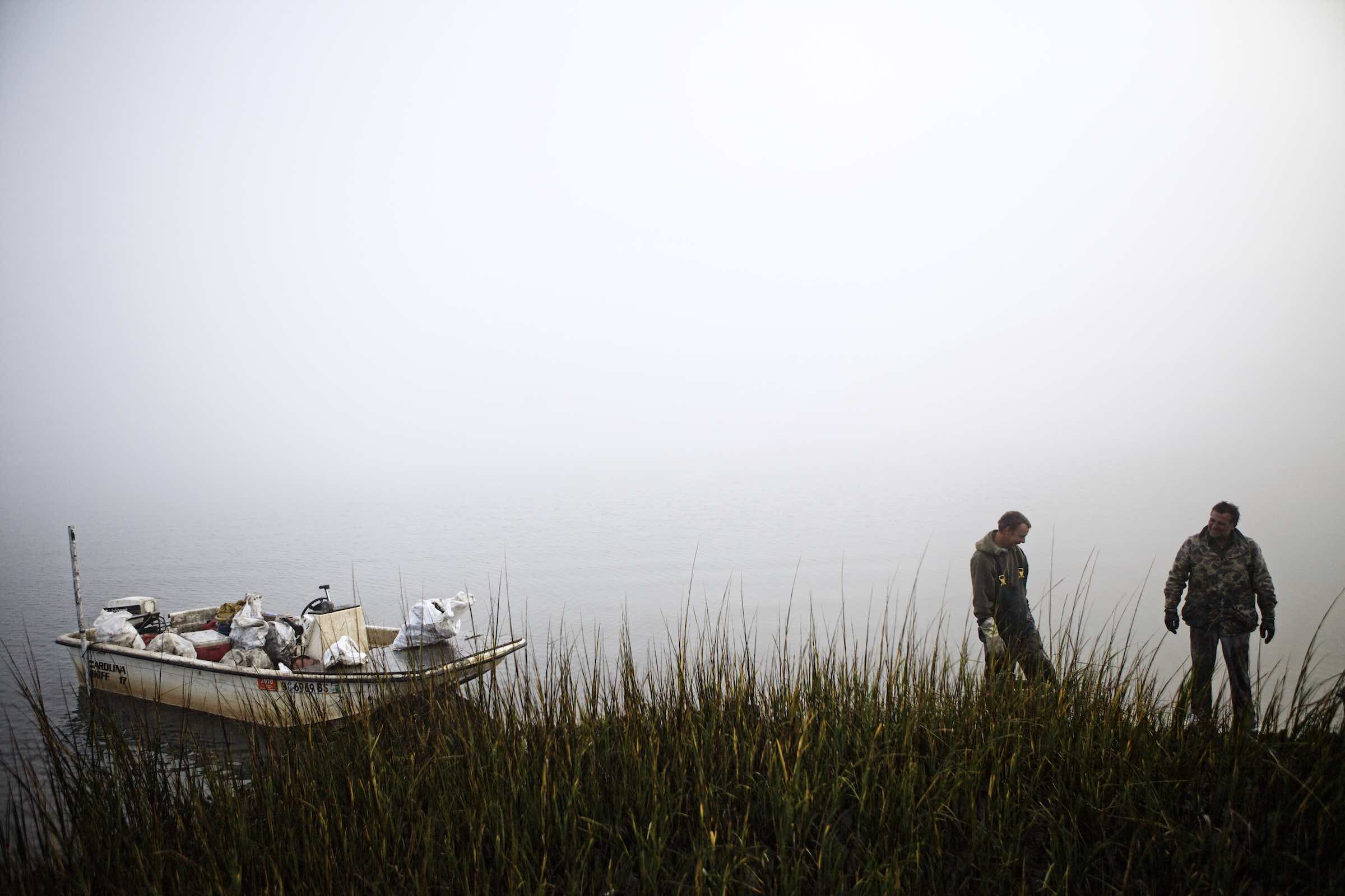 Fishermen and their boat standing behind tall marsh grasses.