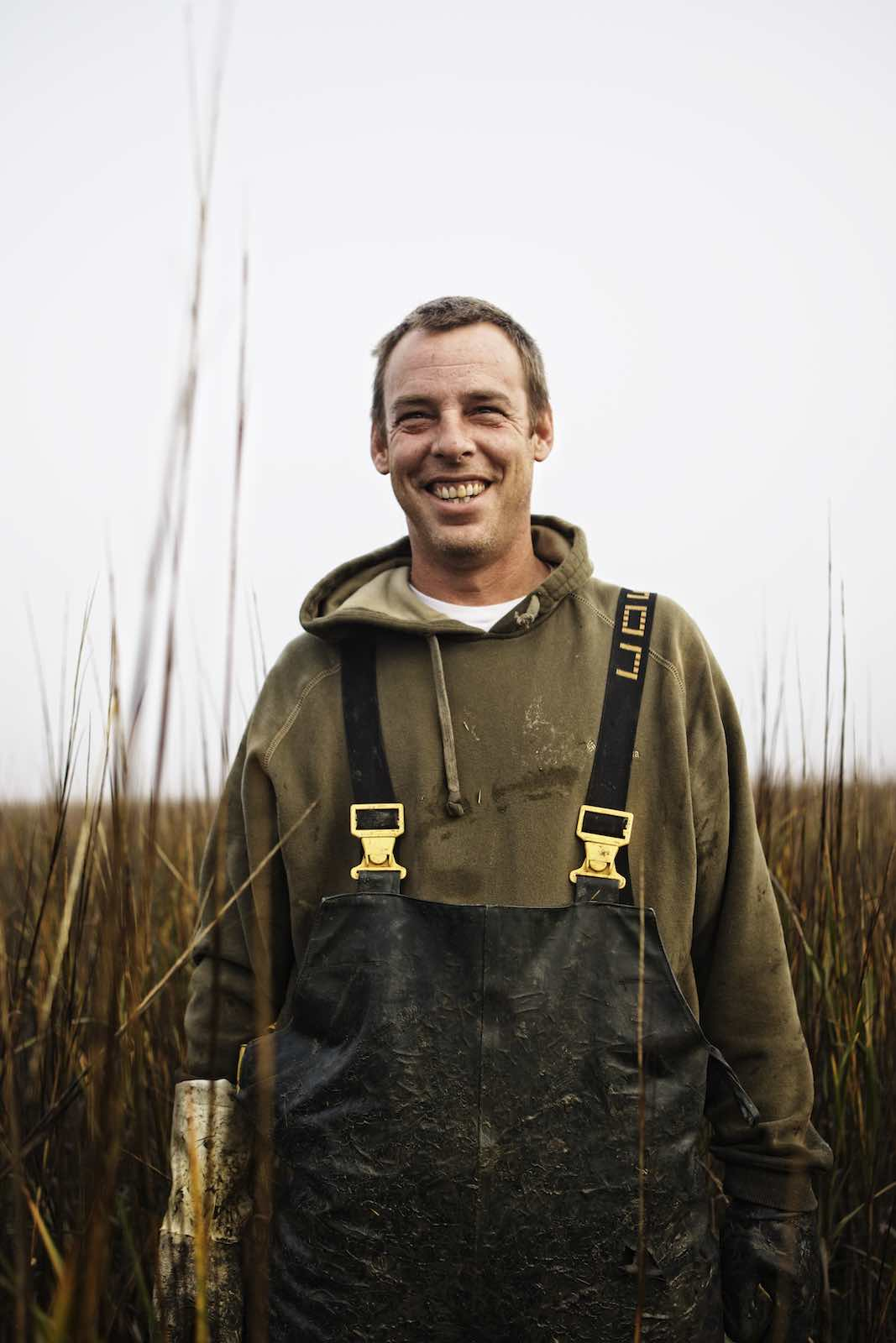 Fisherman standing in marsh grasses and smiling.