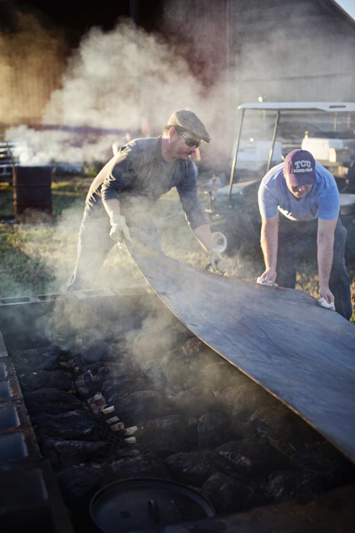 Jody Horton Photography - Men work together to uncover large outdoor barbecue pit.