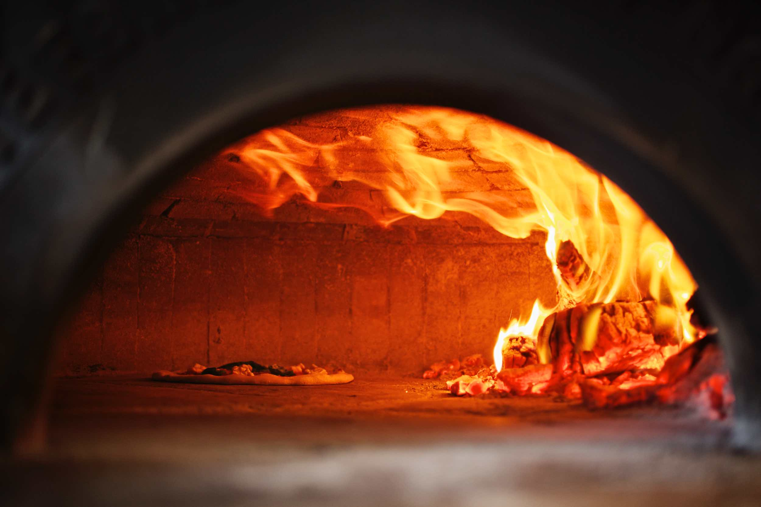 Jody Horton Photography - Pizza cooking inside brick pizza oven.