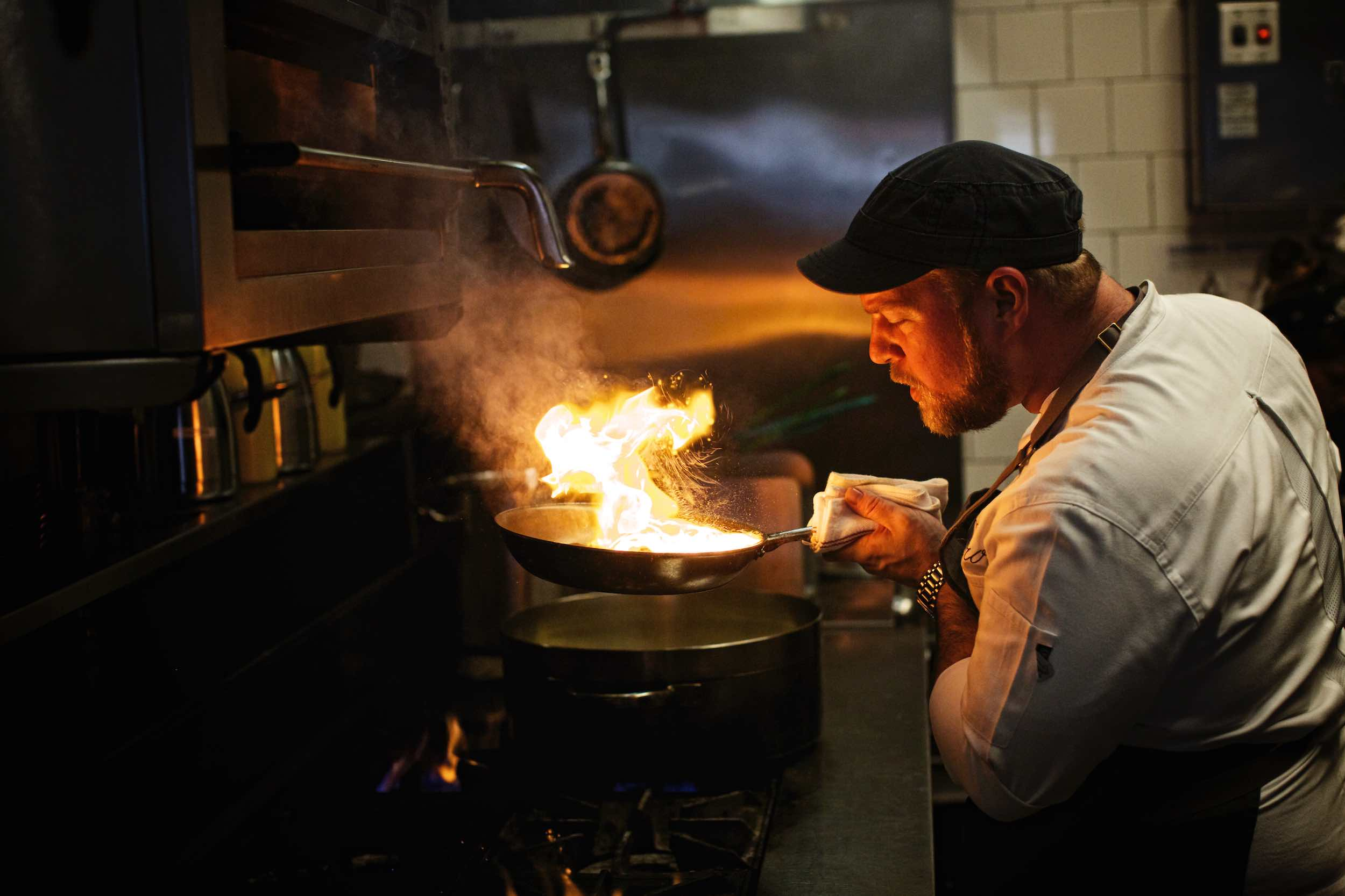 Jody Horton Photography - Chef sauteing with fire in the kitchen.