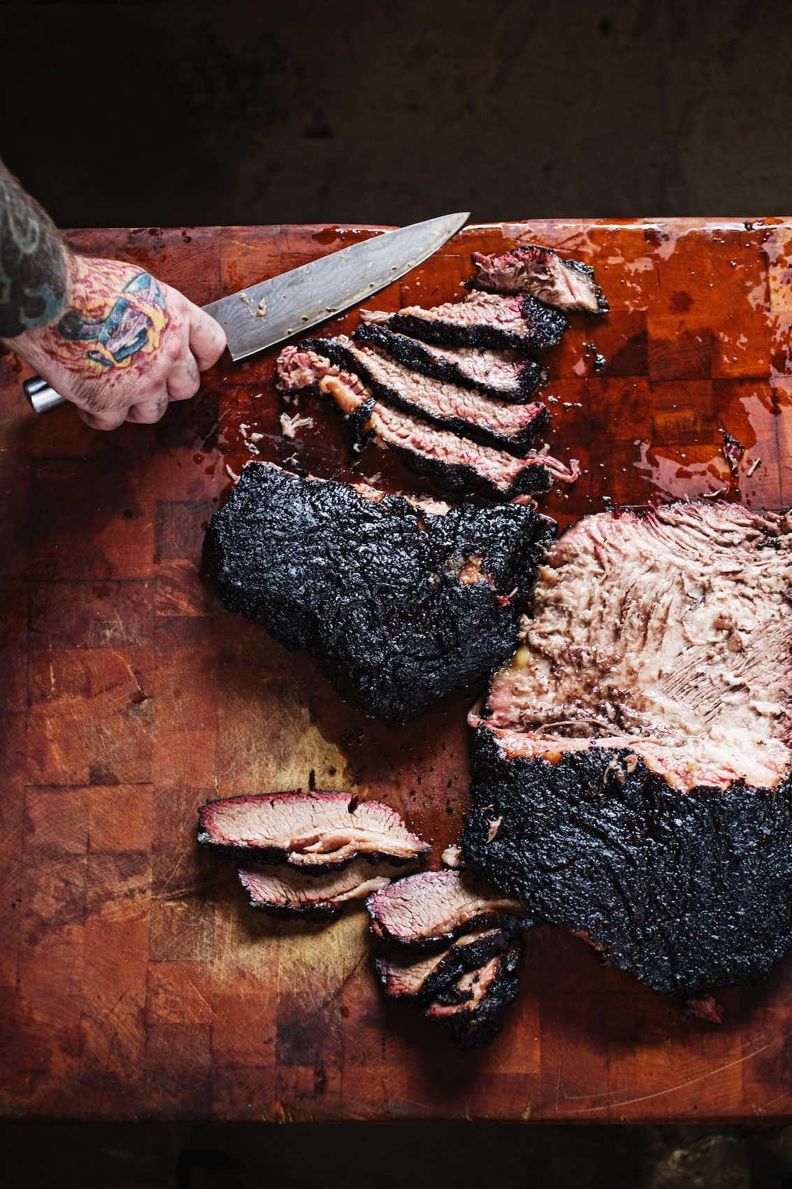 Jody Horton Photography - Blackened brisket sliced on wood cutting board.