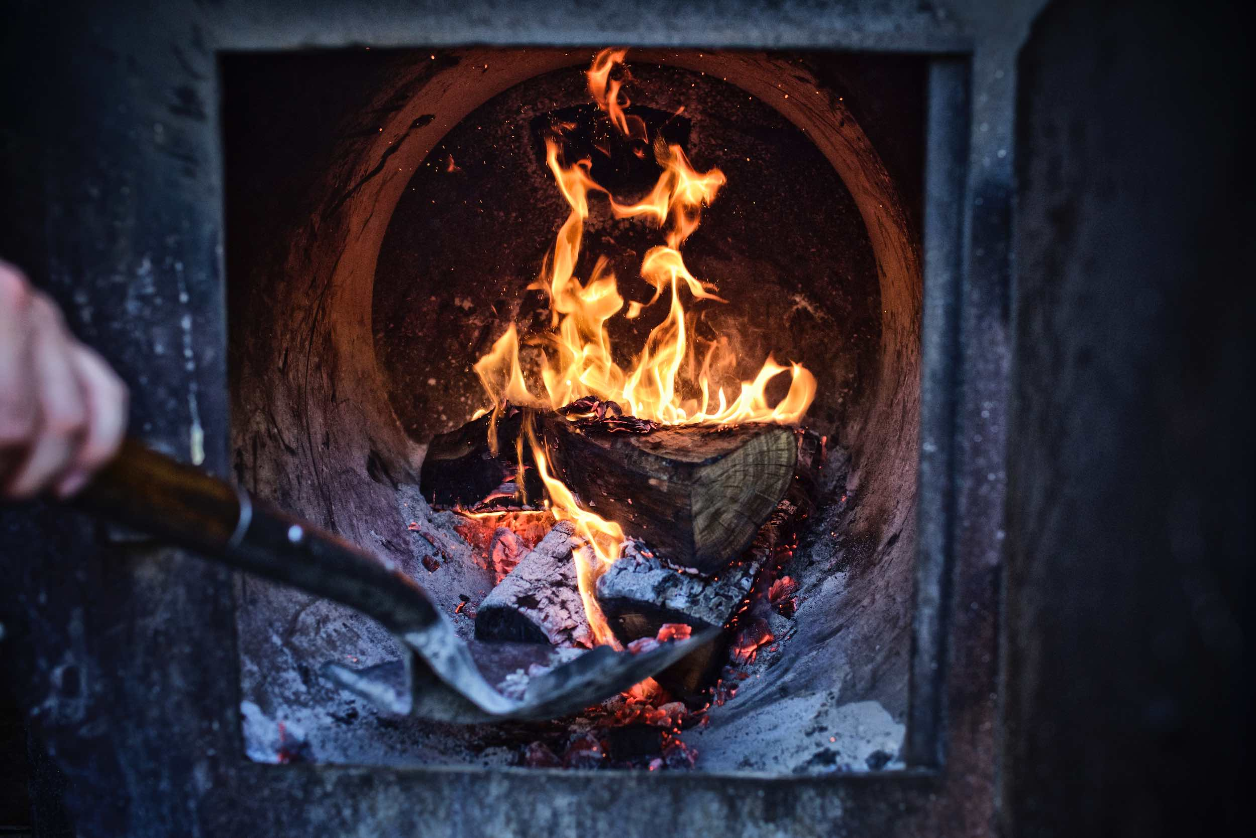 Jody Horton Photography - Stoking wood fire for smoker.