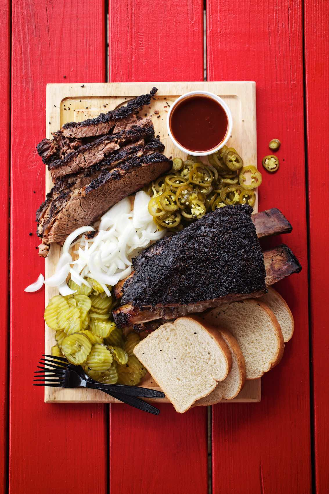 Jody Horton Photography - Barbecue spread on cutting board on red picnic table.