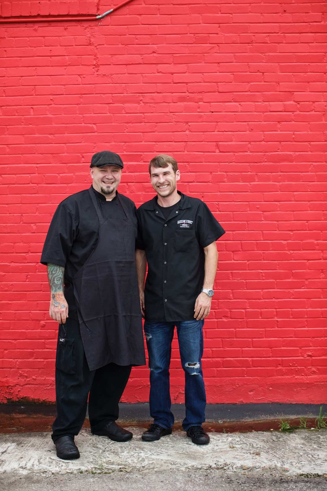 Jody Horton Photography - Chefs standing against painted red brick wall.