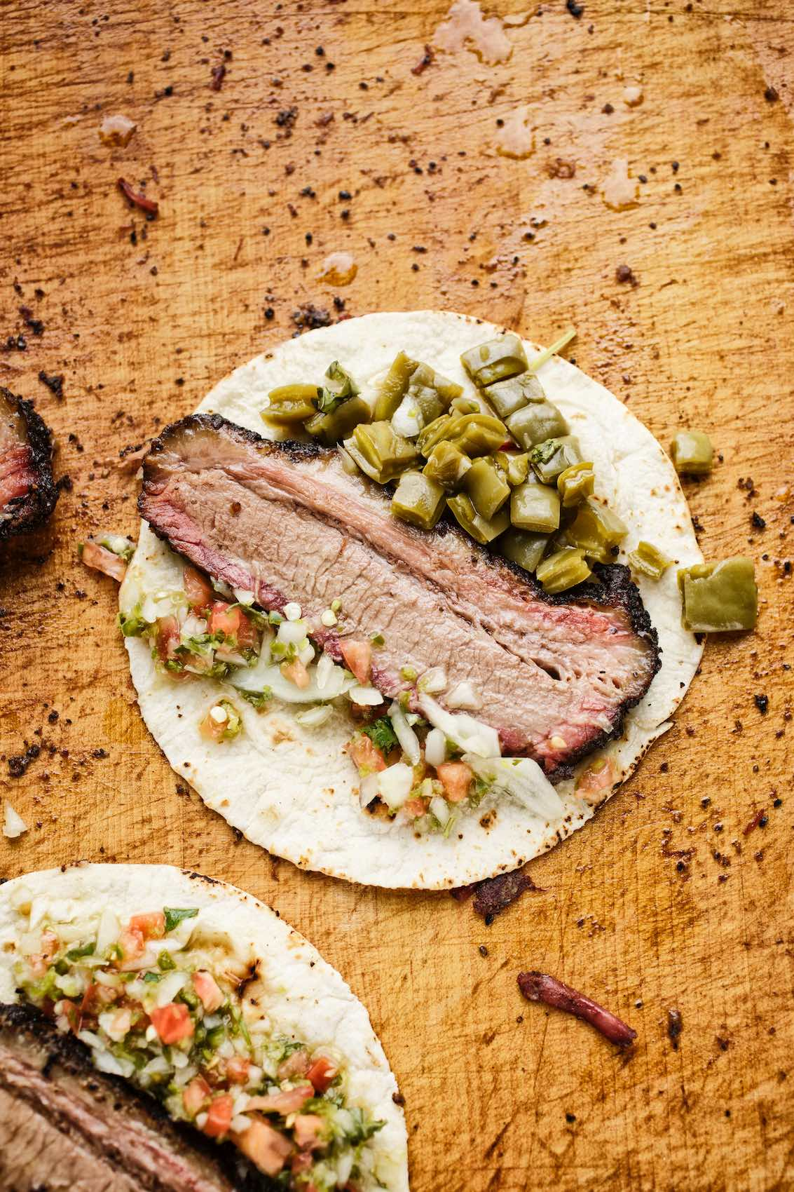 Jody Horton Photography - Brisket taco on wood cutting board.