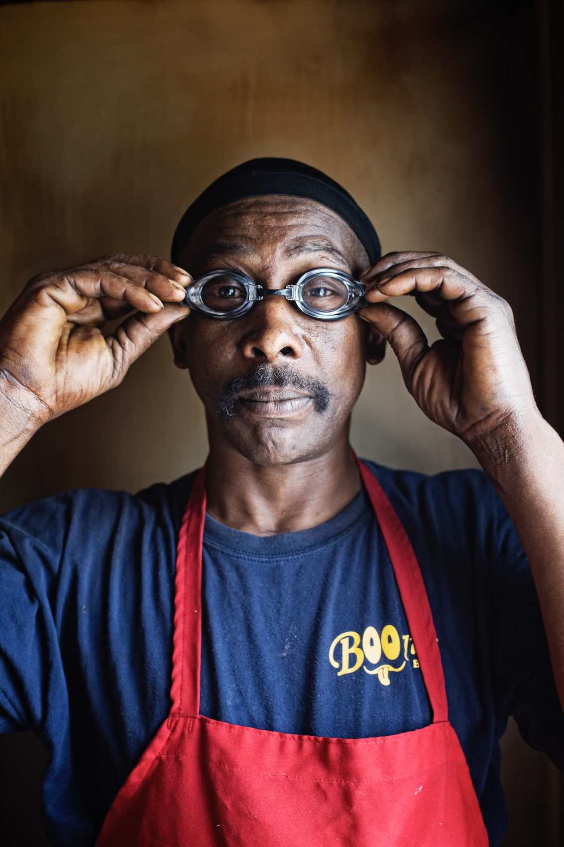 Jody Horton Photography - Portrait of man in red apron putting on goggles.