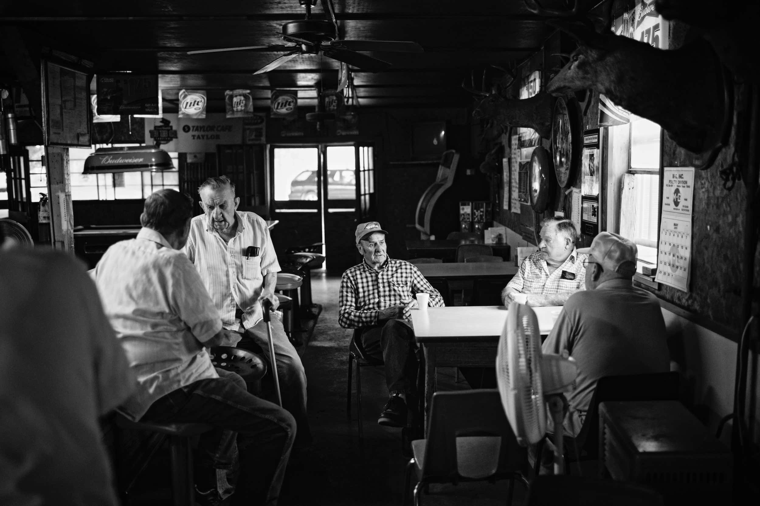 Jody Horton Photography - Elderly men chatting in restaurant dining room, shot in B&W.