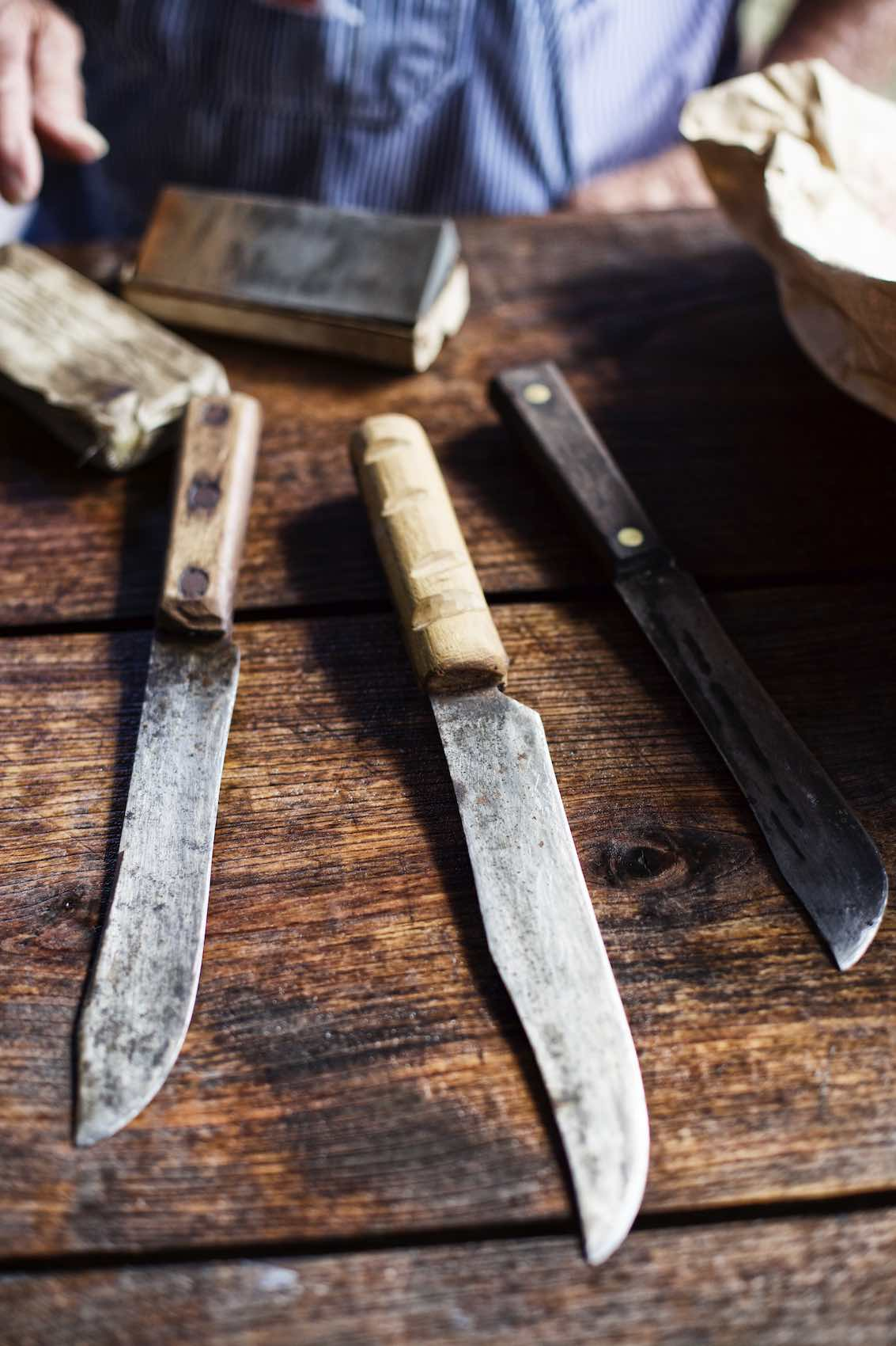 Jody Horton Photography - Assorted, rustic knives on wood table.