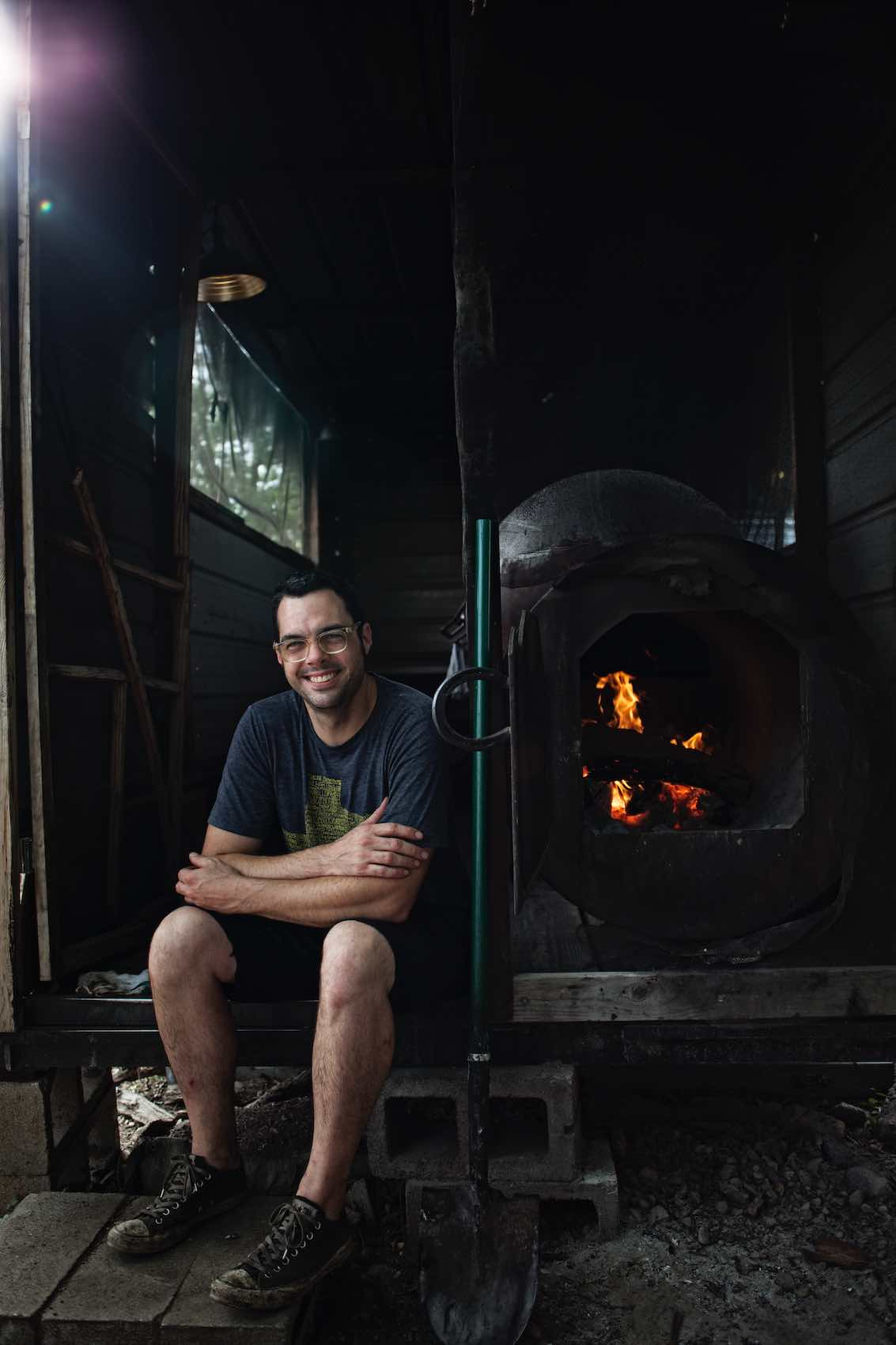 Jody Horton Photography - Aaron Franklin sitting next to barbecue smoker.