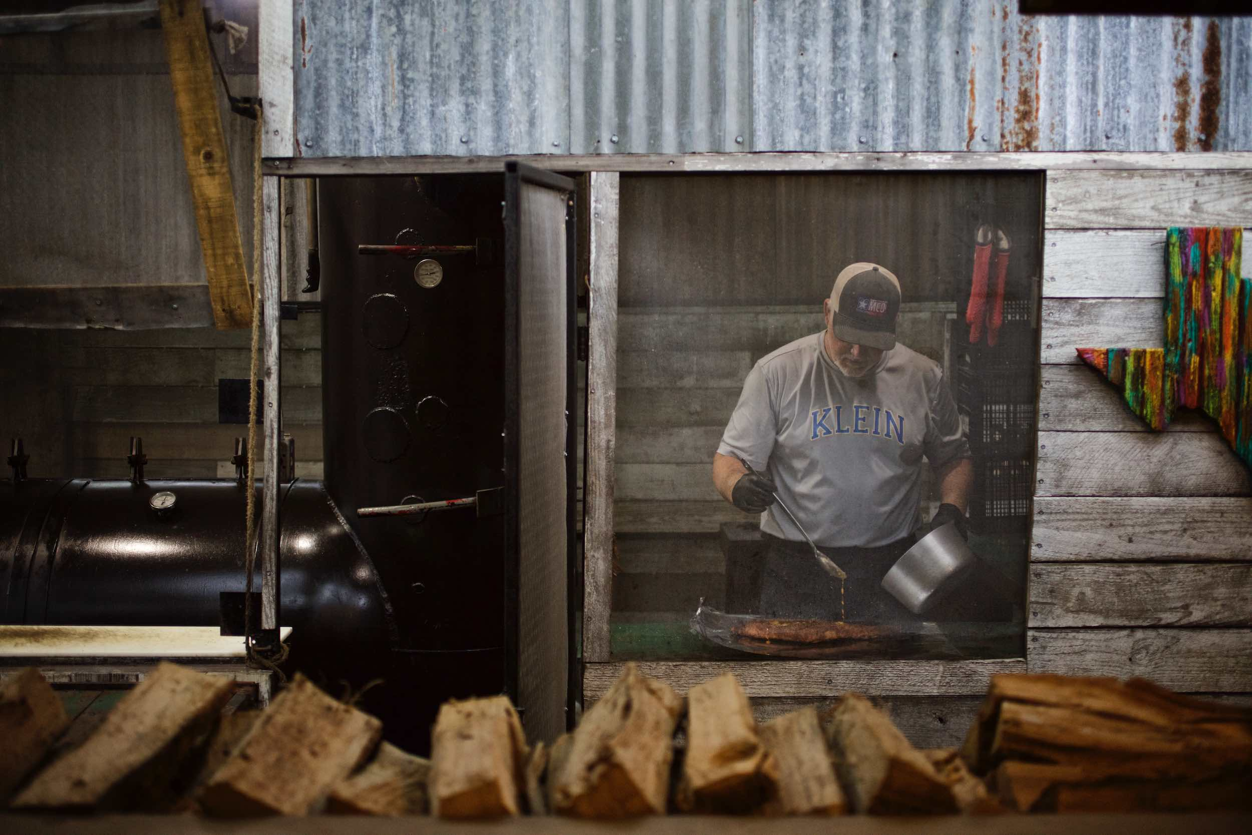 Jody Horton Photography - Man preparing meat behind mesh window of rustic building.