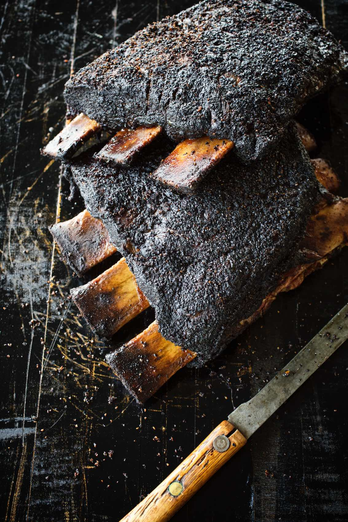 Jody Horton Photography - Blackened ribs on cutting board with rustic knife.