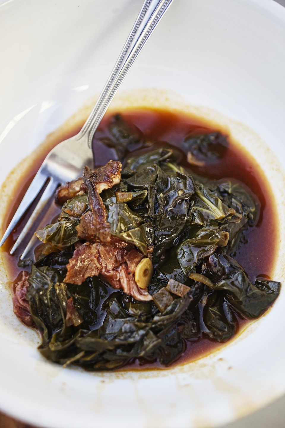 Jody Horton Photography - Stewed collards and meat in a shallow bowl.