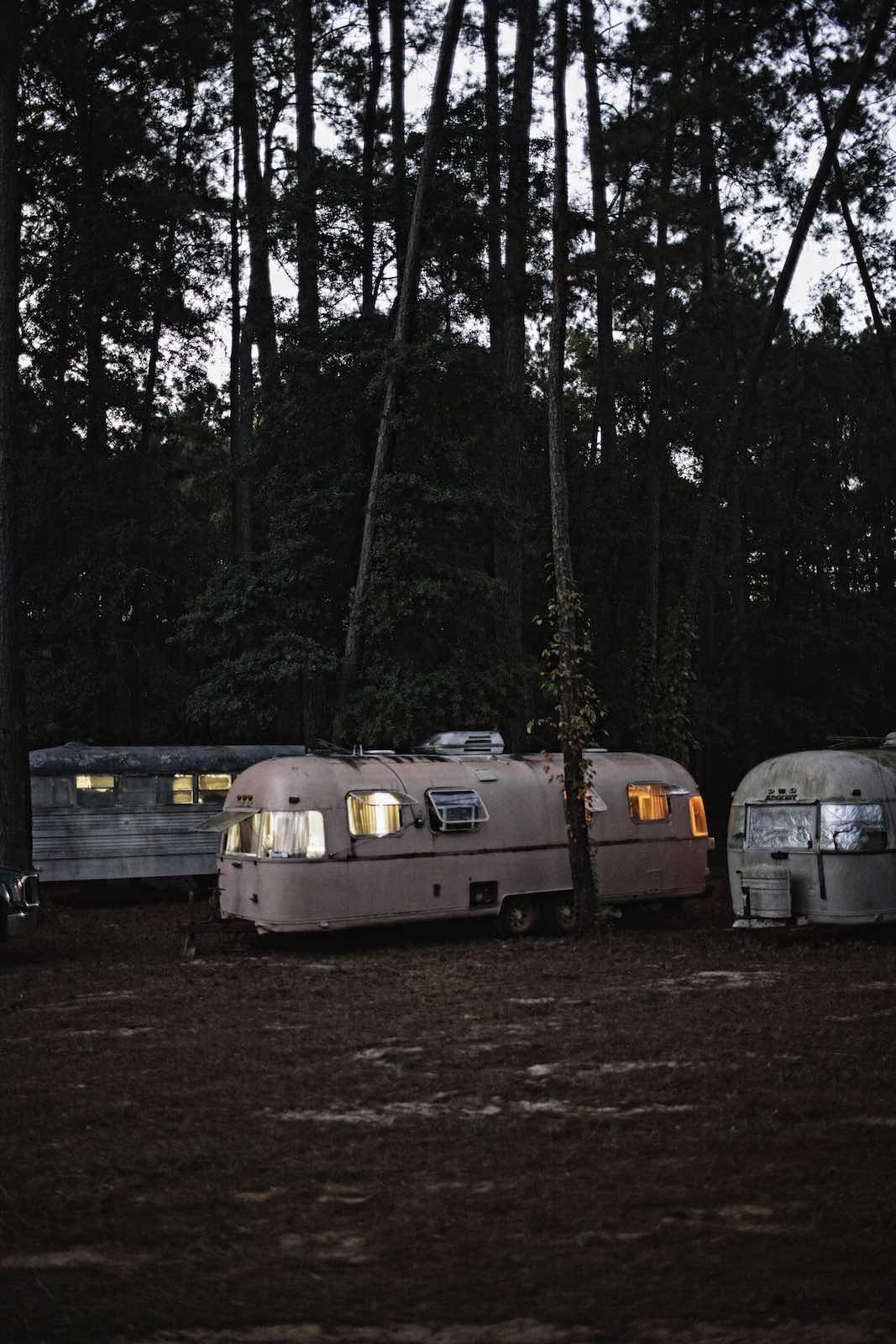 Jody Horton Photography - Vintage campers parked under trees at dusk.