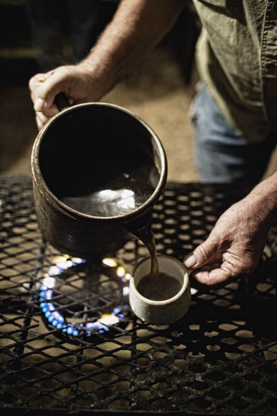 Coffee heating on a stove in a pitcher and pouring into a small mug.