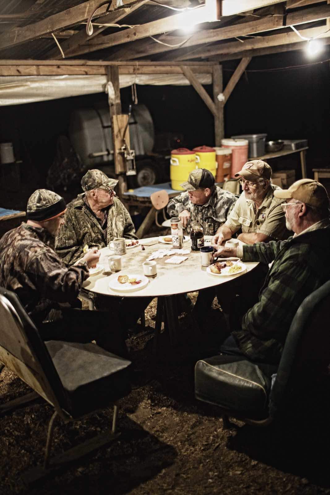 Jody Horton Photography - Hunters eating at a round table in the dark, early hours of the morning.