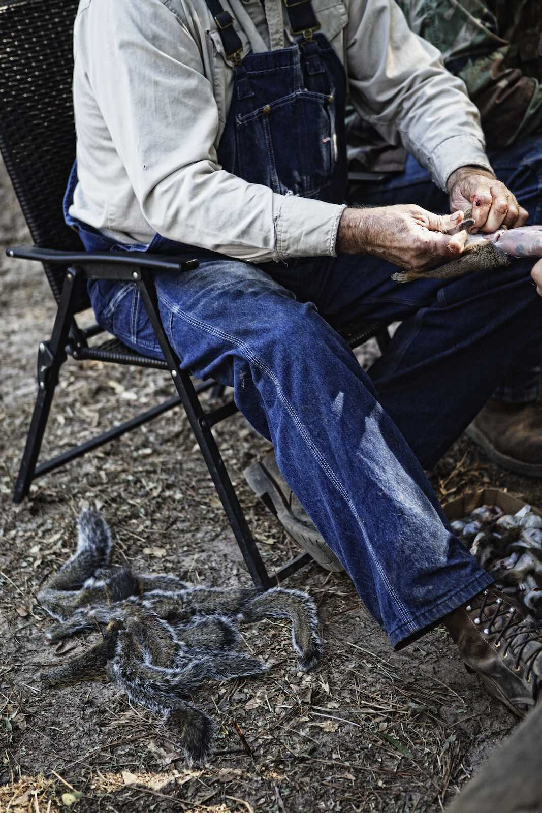 Jody Horton Photography - Hunter sitting next to squirrel tails while skinning the hunt.