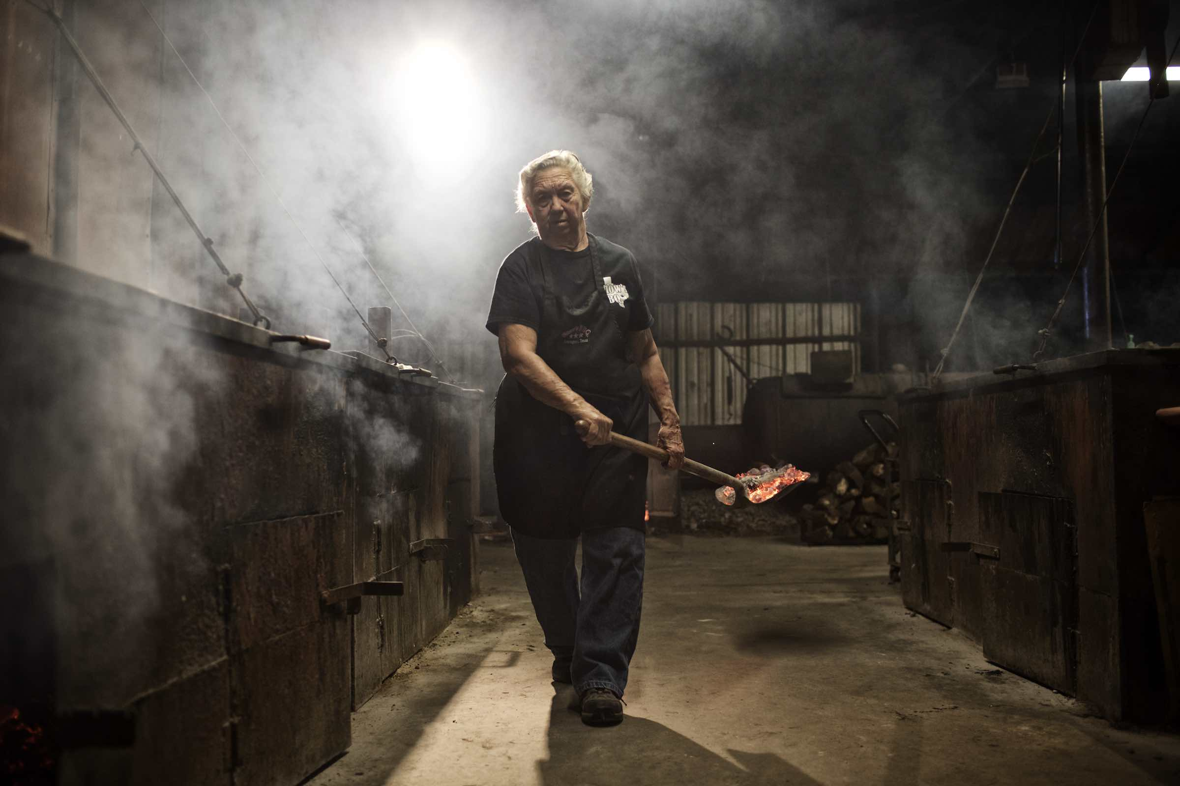 Pit master carrying hot coals on a shovel.