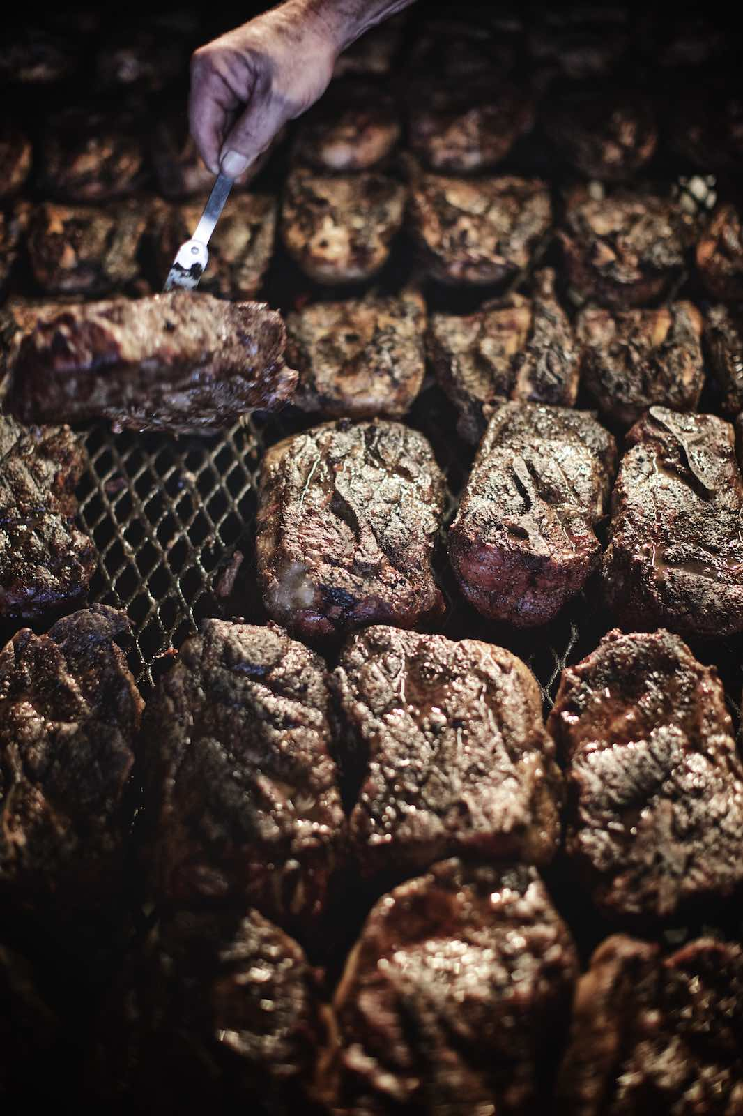Jody Horton Photography - Various cuts of beef cooking on a grill grate.