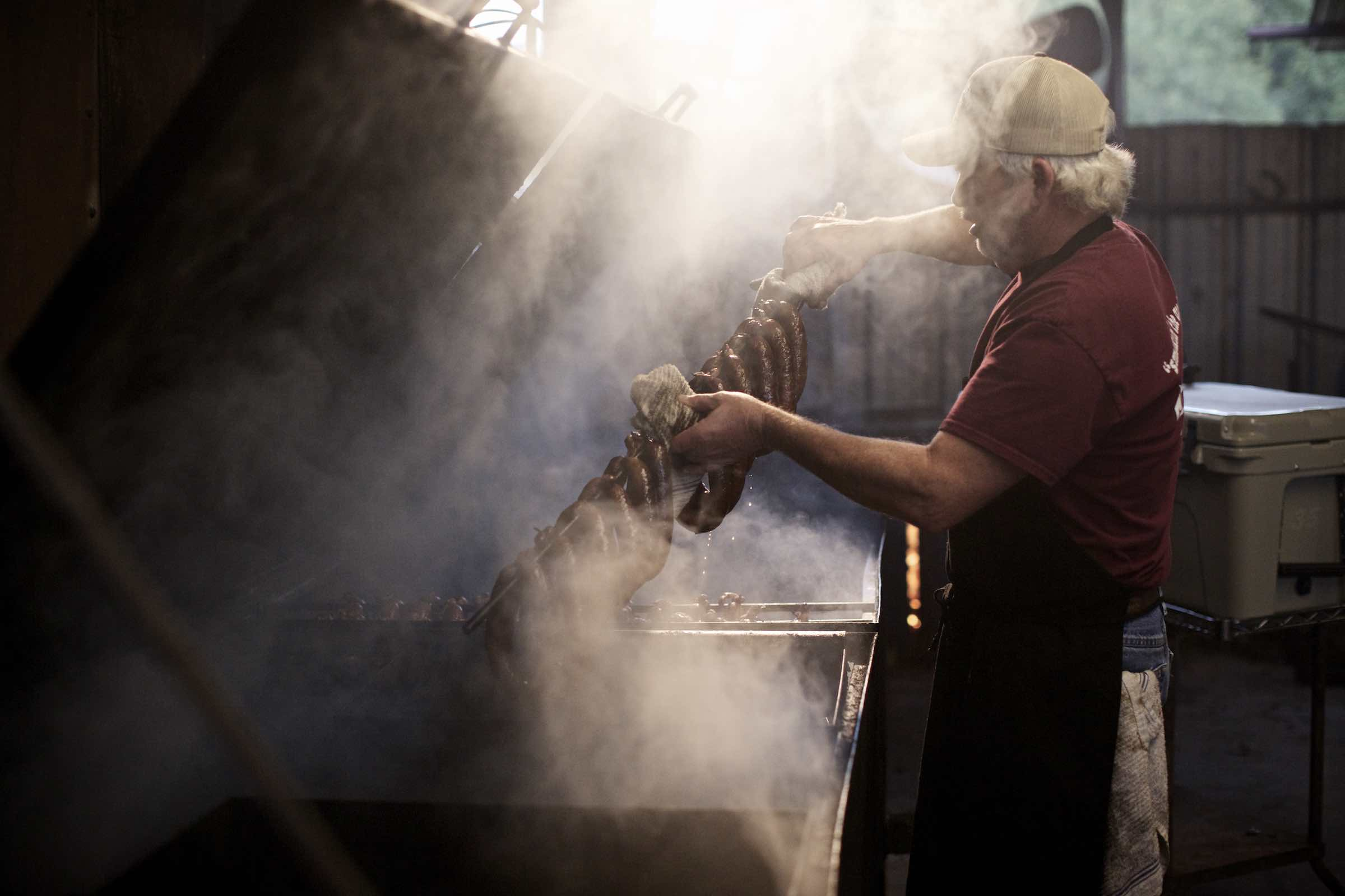 Pit master removing smoked sausages from smoker.