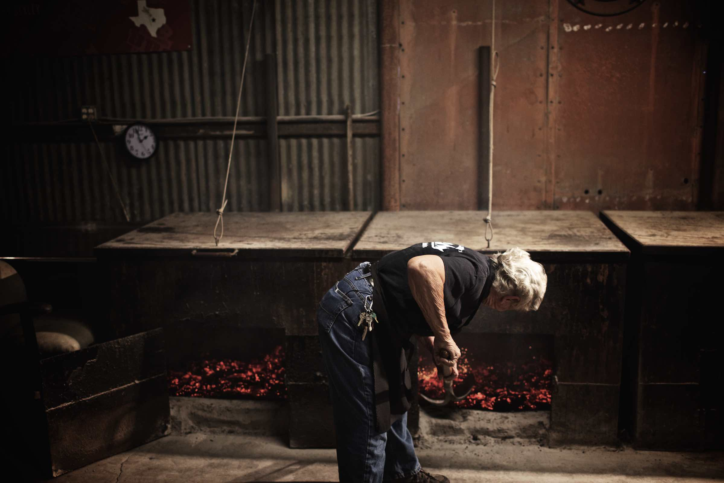 Jody Horton Photography - Pit master shoveling hot coals underneath barbecue smokers.