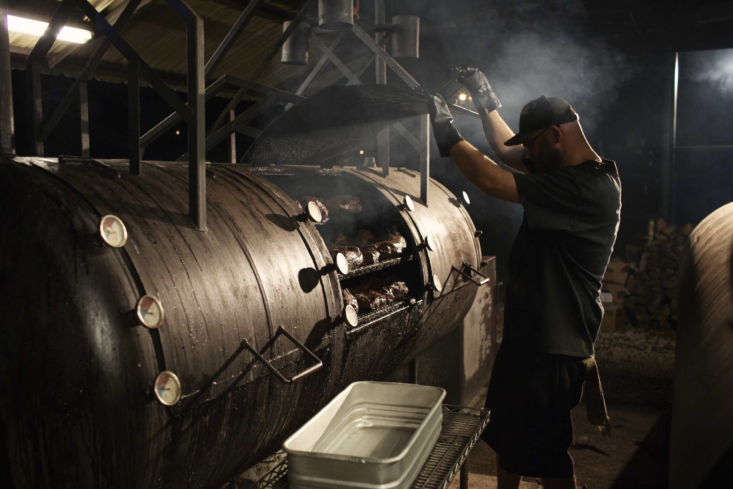 Jody Horton Photography - Young pit master observing meats cooking in a large smoker.