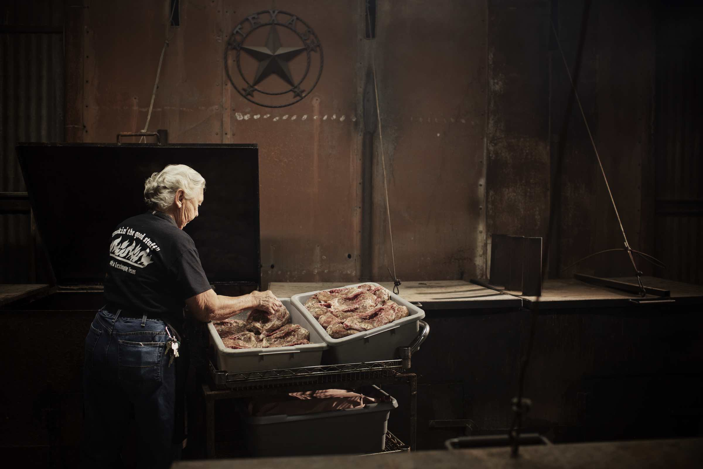 Pit master handling large cuts of seasoned meat in beige tubs.